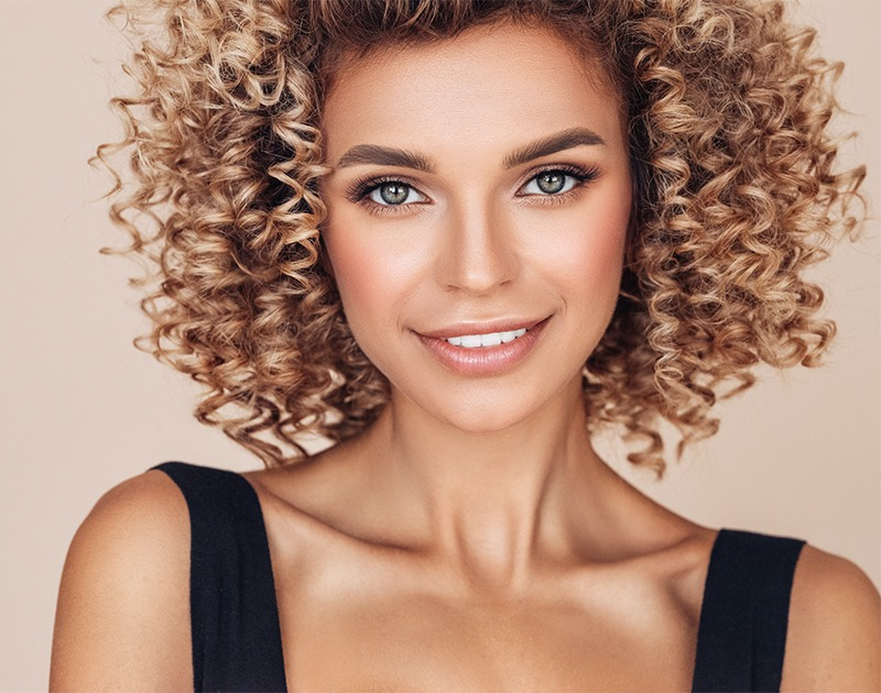 Beautiful young woman of ethnicity, smiling with curly hair
